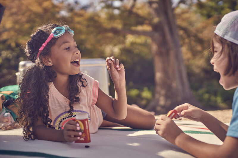 Two children sitting outdoors eating Sun-Maid raisins